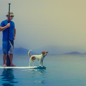 Man Paddling with Dog